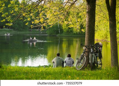 The concept of summer family active recreation. The couple sitting near the lake with boats  after a bicycle ride, leaning their bicycles to a large tree