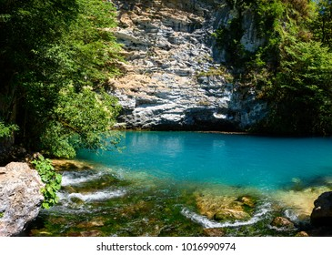 Concept of summer nature. Amazing view of blue mountain lake like paradise, rock wall and colorful water. Scenery of Abkhazia natural paradise with awesome closeup perspective and fast stream.