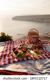 Concept of a summer picnic outdoors with blanket, eco style straw bag with  plate of fruits, cheese and wine. Romantic picnic with seaside and mountain view at sunset - Shutterstock ID 1895110717