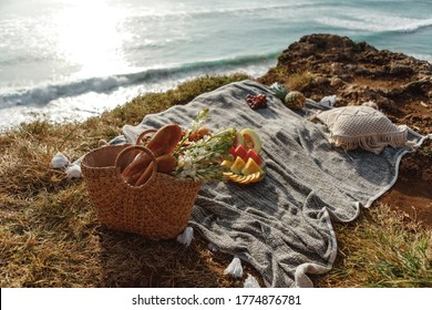 Concept of a summer picnic outdoors in a green park with blanket, eco style straw bag with flowers and baguette bread, plate with fruits. Romantic picnic with seaside and mountain view at sunset