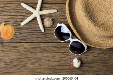 Concept Summer. Starfish, Hat and Sunglass on Wood Texture