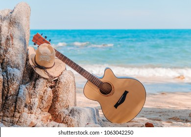 Concept of summer traveling with guitar on beach background, laying on rocks. Hat on guitar leaning on beach rocks