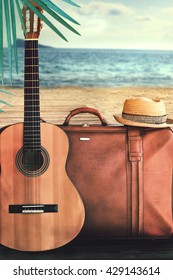 Concept of summer traveling with old suitcase and guitar on blur beach background.
