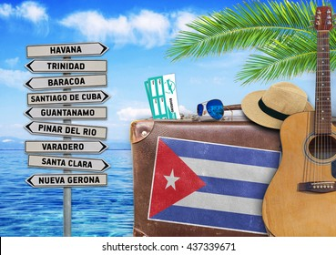 Concept of summer traveling with old suitcase and Cuba town sign
