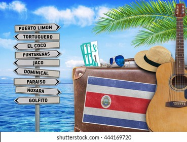 Concept of summer traveling with old suitcase and Costa Rica tow