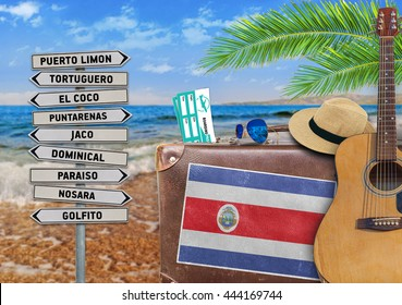 Concept of summer traveling with old suitcase and Costa Rica town sign