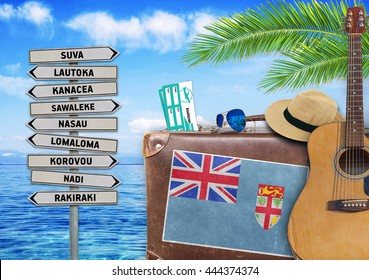Concept of summer traveling with old suitcase and Fiji town sign