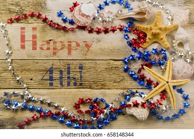 Concept for summer United States holiday of fourth of July on the beach with shells, starfish, sand and red white and blue decorations. Text added.