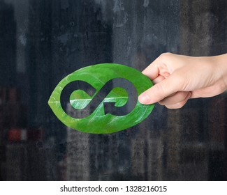 Concept of supply technologies for green Eco-friendly and circular economy, female hand holding a leaf with hole of arrow infinity recycling shape.