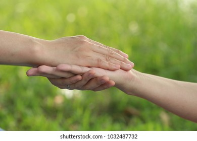 concept of support , man and woman holding hands on green nature background