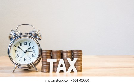 Concept tax time and alarm clock with coins stack on wood table, copy space