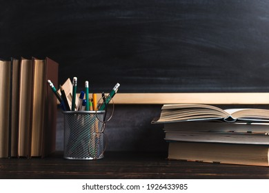 Concept to teacher's day. Pens, pencils, books and glasses on table, against the background of chalkboard. Back to school, copy space.