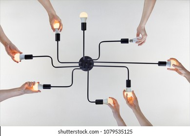 Concept of team spirit, or teamwork on example of team work when replacing LED lamps in a ceiling chandelier.