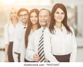 concept of team work - the leader and the business team standing one behind the other
