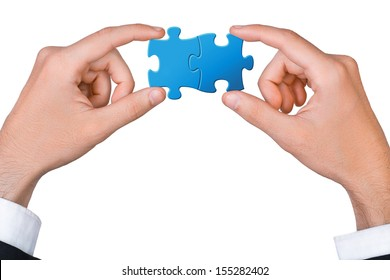 Concept of teamwork - hands connect two puzzle pieces