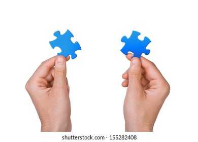 Concept of teamwork - hands keep two puzzle pieces