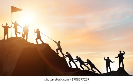 Concept of teamwork with team climbing mountain top