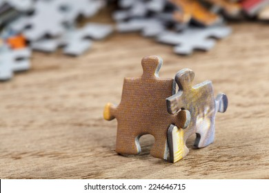 Concept of teamwork: Two jigsaw puzzle pieces on a table joint together. Shallow depth of field