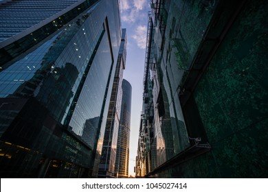 concept: technology, future, downtown. wide-angle modern cityscape with glass skyscrapers at sunset golden hour.