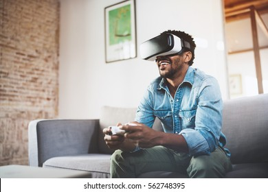 Concept of technology,gaming,entertainment and people.Happy african man enjoying virtual reality glasses while relaxing on sofa.Smiling young guy with VR headset playing video game at home.Blurred