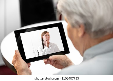 Concept Telemedicine and distance treatment, elderly woman holding a tablet with a female doctor