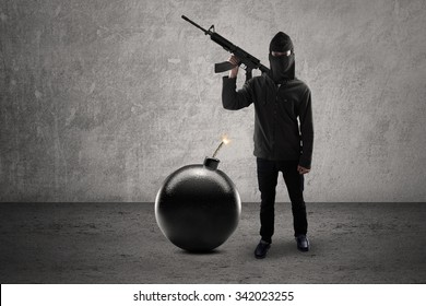 Concept of terrorism. Male rebel wearing dark clothes and mask, carrying rifle with bomb