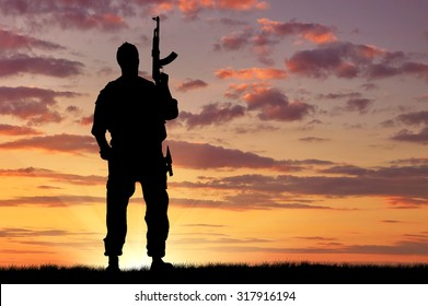 Concept of terrorism. Silhouette of a terrorist with a weapon at sunset