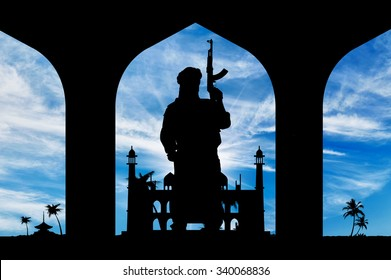 Concept of terrorism. Silhouette of a terrorist with a weapon on the background of the town hall