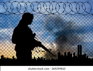 Concept of terrorism. Silhouette terrorists near the border fence in the background on the city in smoke at sunset