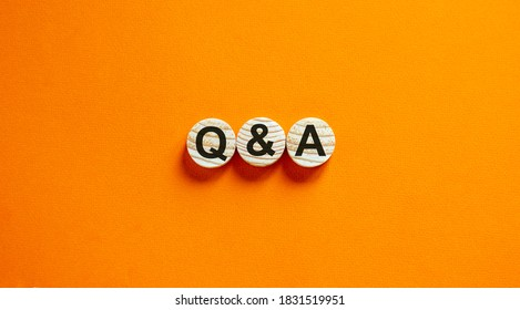 Concept text 'Q and A' on wooden circles on a beautiful orange  background. Business concept. Copy space.