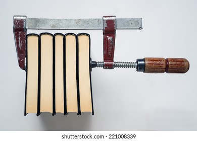 Concept that illustrate the traditional books printing, using the action of Presss with the screw clamp. White background