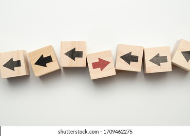 Concept of think differently - wooden cubes with arrows. Close up.