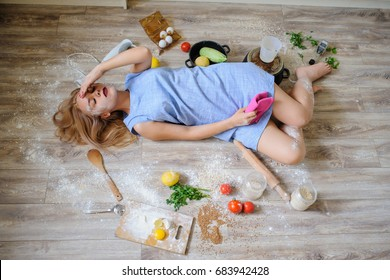 Concept: top view of desperate housewife lying on the floor in her kitchen with flour on her face