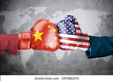 Concept of trade war between USA and China. Two hands of wearing boxing gloves with China and USA flag over world map