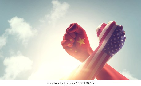 Concept of trade war between USA and China. Two fists hitting each other over sky background and sunlight with copy space.