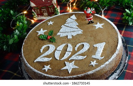Concept with traditional Greek new years cake,vasilopita, decorative with a mistletoe and a saint claus, red tassels,artificial pine and red berries sticks around