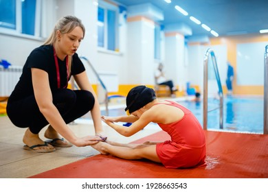 Concept training swimming child. Little kid girl is doing exercises with trainer before learn in pool, muscle stretching.