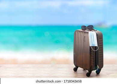 Concept of travel during pandemic time. Suitcase with protection mask on the beach