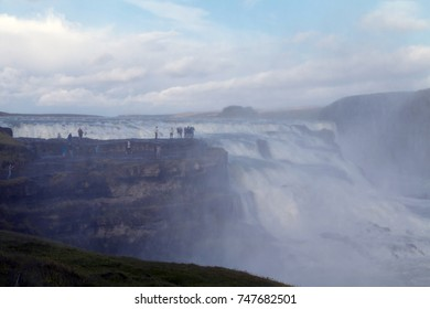 Concept of travel, exploring and sharing experience. People above the waterfall in water splash cloud taking video or photo. Gullfoss - famous icelandic waterfall. Defocused.