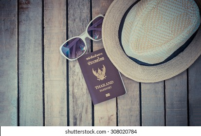 The concept of travel, hats, sunglasses, passport on wood. Get ready to travel