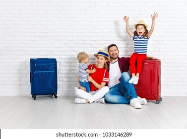 concept travel and tourism. happy family with suitcases near empty wall