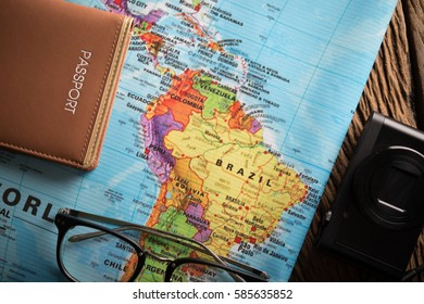 Concept of travel - View of camera eyeglasses notebook and map on wooden background, Travel and Holiday with vintage tone.
