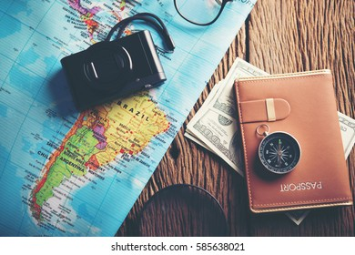 Concept of travel - View of Traveler magnifier,camera eyeglasses money and items, Travel and Holiday on world map background vintage tone.