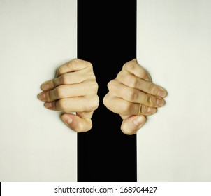 Concept of two hands trying to open a slit to exit from the darkness
