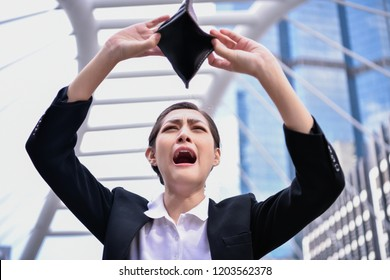 Concept of unemployed. Asian businesswoman is opening empty wallet. Young business woman is stressed because of no money.