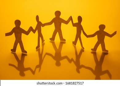 Concept of unity and humanity of people where paper men hold hands