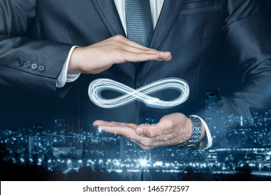 Concept of unlimited Internet. Businessman shows sign of infinity on the background of the city. The concept of unlimited Internet.
