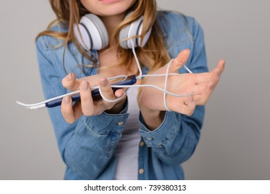 Concept of unnecessity, obsolescence, inconvenience of using wired headphones. Angry and irritated teenage girl holding cell and showing  tangled wire of her headphones