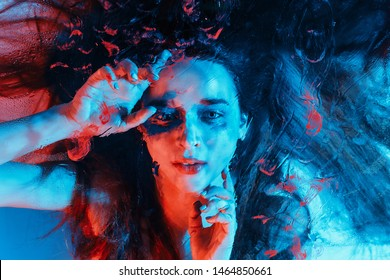 Concept of unrealistic art shooting of a mermaid under water. Red haired girl like a mermaid with under water effects. with red blue color art portrait