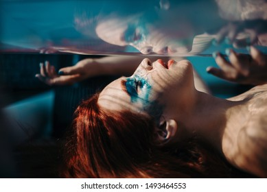 Concept of unrealistic art shooting of a mermaid under water. Red haired girl like a mermaid with under water red blue color effects. art picture close up view from under the glass